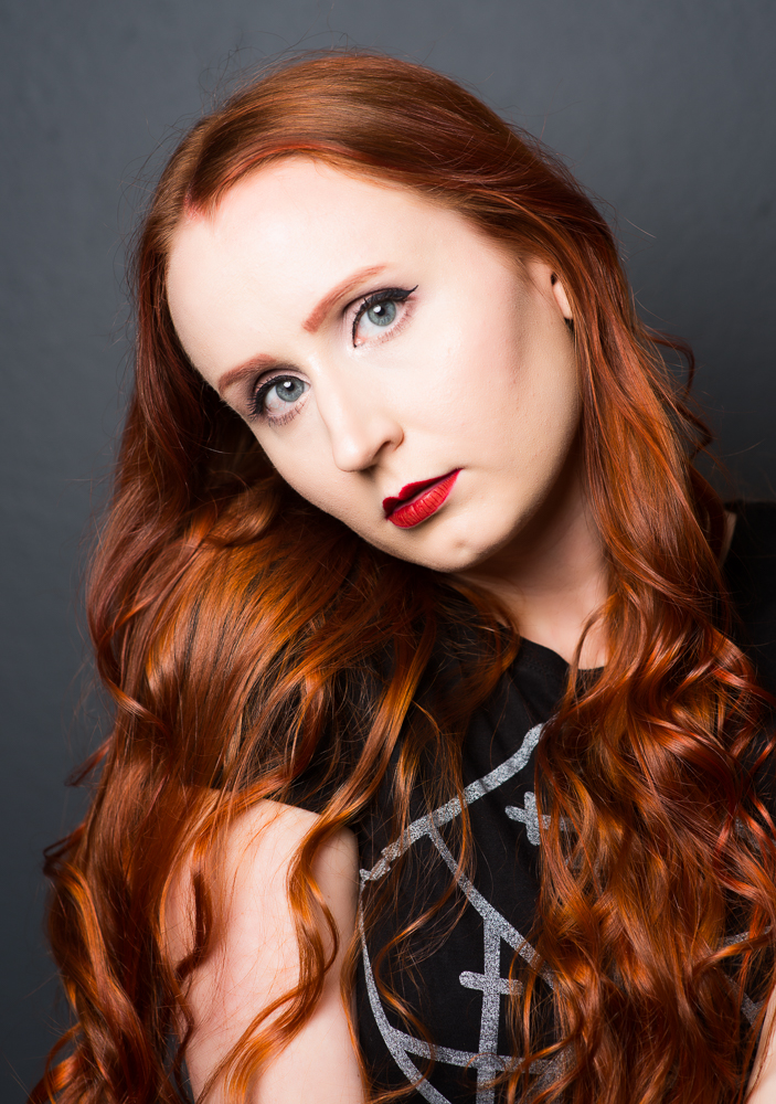 Young woman with long curly auburn/red hair